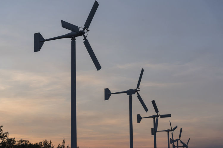 Low Angle View Of Wind Turbines Against Sky During Sunset