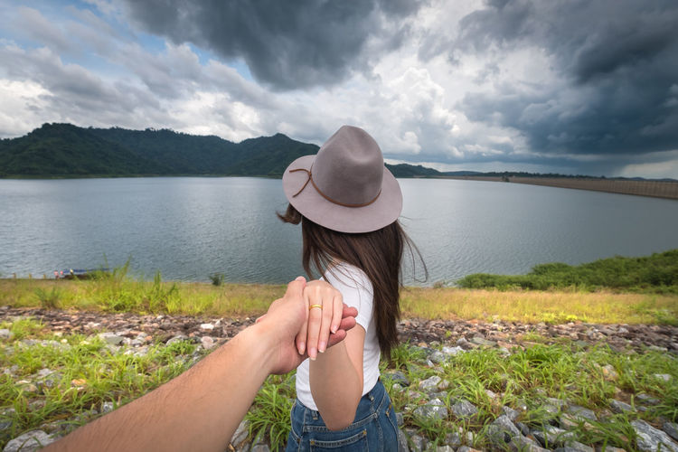Cropped Image Of Man Holding Women Hand At Riverbank Against Cloudy Sky