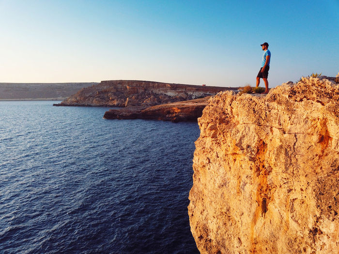 Man standing on cliffs by sea against sky