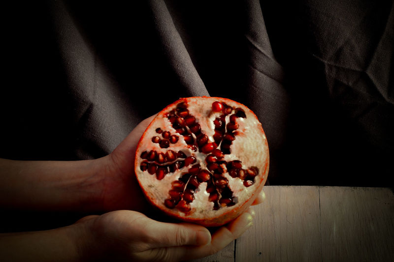 Close-up of hand holding pomegranate over black background