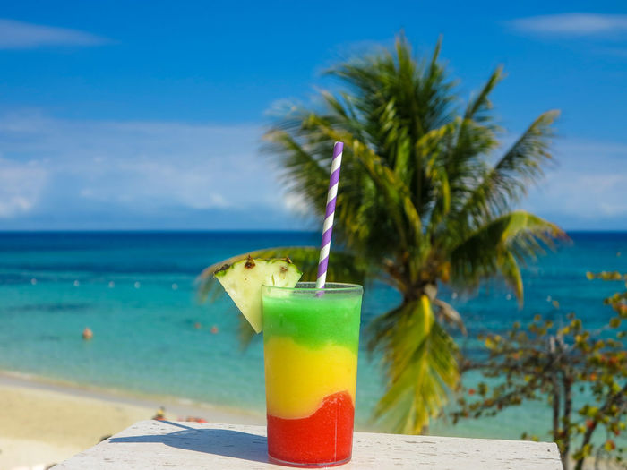 Multicolored cocktail on table with palm tree and blue sky Drinking Straw Glass Cocktail Caribbean Sky Blue Relaxing Sea Holiday Vacation Red Yellow Green Blue Sky Pineapple Alchohol
