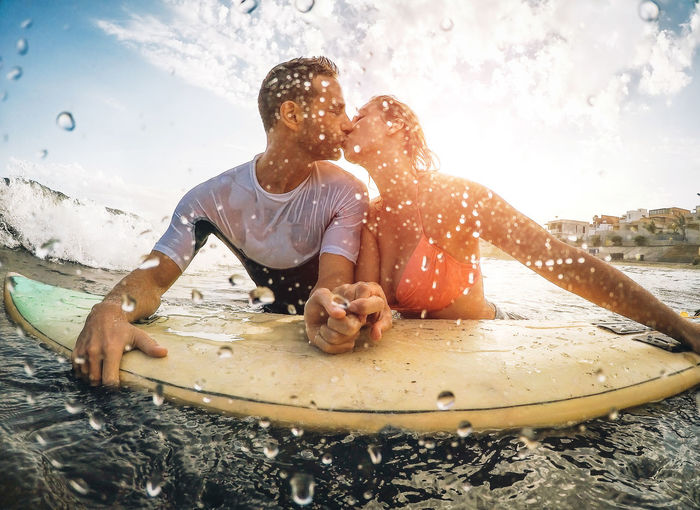 Couple Kissing While Leaning On Surfboard In Water At Beach