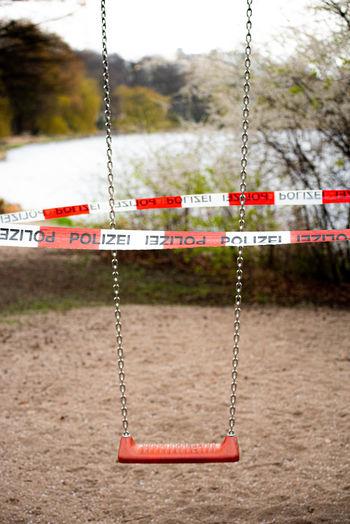 Cordon tape around swing at playground