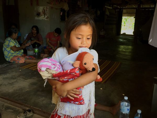 A young girl holds tightly to her hand-me-down clothing and her new friend. The children here eat rice for every meal. Sometimes they can add oil and salt to flavor their rice, but this is considered a luxury. As a refugee she, and the other children here, have no rights to healthcare or education. Fortunately the children are able to receive an education by a small, custom purpose daycare close by. To be given a gift - something as simple as a stuffed animal - she is not only overjoyed and thankful but she is also given the chance to feel like a child; to play and care for her new stuffed friend. There is no telling where the girl and her monkey will go or what adventures she will dream up for them. The Human Condition Volunteering Volunteer Donation Donations  Children Charity Open Edit Helping Refugees Untold Stories Eyeemphoto
