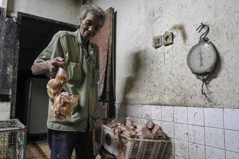 Senior Man Holding Chicken In Butcher Shop