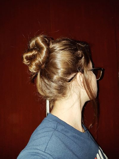 Close-up of woman with hair bun against wall