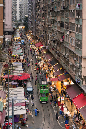 High angle view of people on city street amidst buildings