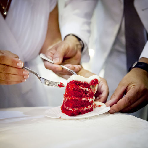 Midsection of bride and groom holding cake slice in plate