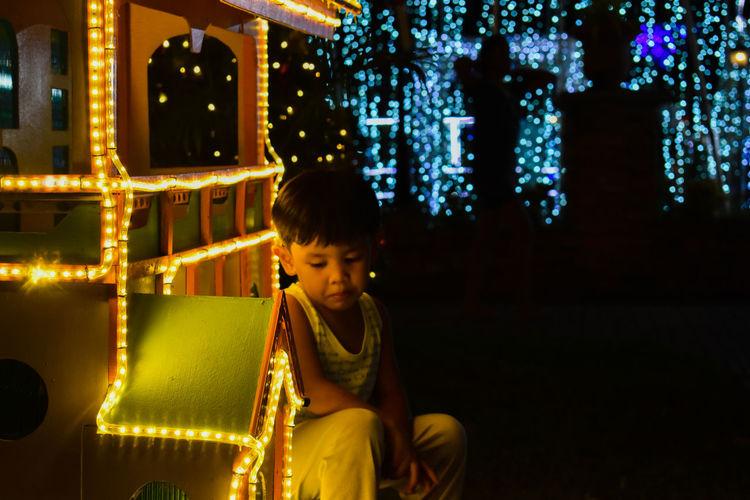 Full length of boy looking at illuminated night