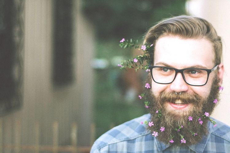 Close-Up Of Smiling Hipster Wearing Flowers