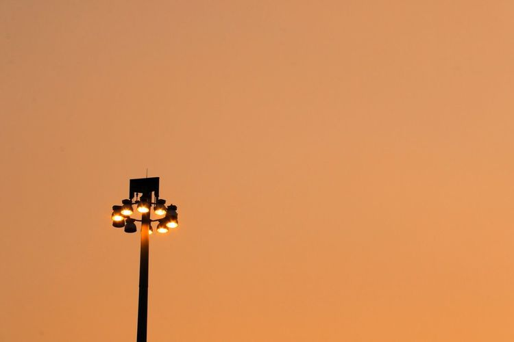 Low angle view of illuminated street light against orange sky
