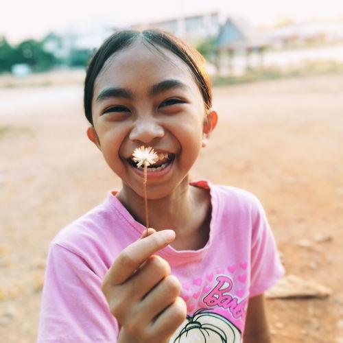 Portrait of smiling girl holding dandelion outdoors