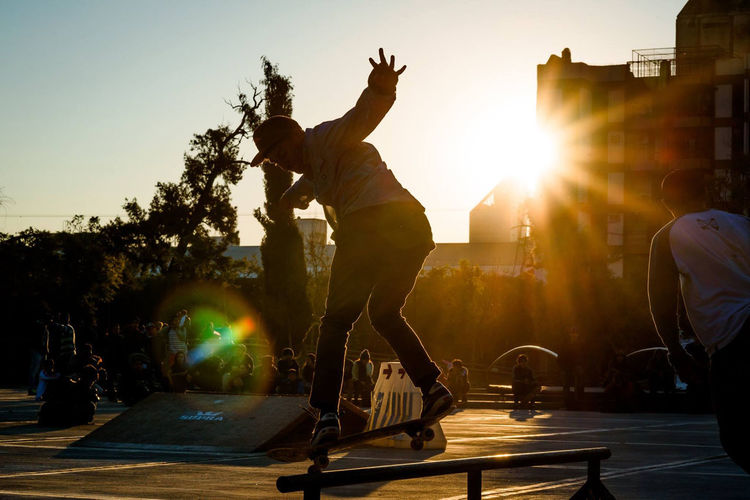 People Looking At Man Skateboarding During Sunset In City