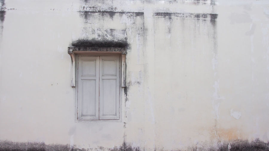 Antique house window in Phuket old town Old Weathered Architecture Building Exterior Built Structure House Window Wall - Building Feature Dirty Exterior Texture Grey Frame Antique White Facade Building Travel Ancient Retro History Structure Cement