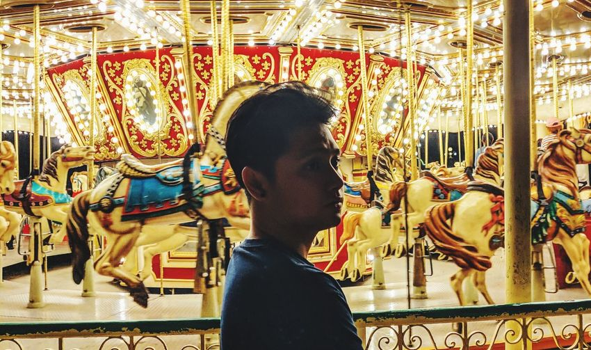 Side view of boy looking at carousel in amusement park