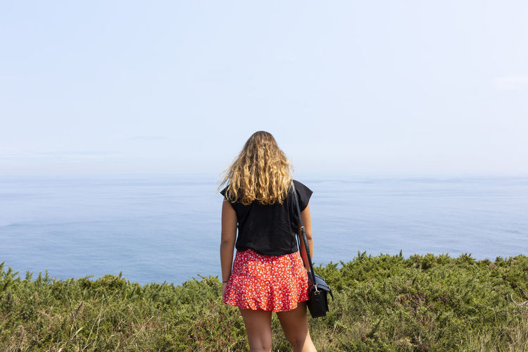 Rear view of woman standing by sea against sky