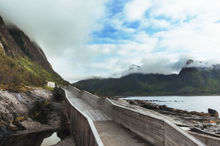 Footbridge Leading Towards Mountains By River