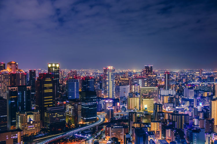 Illuminated buildings in osaka city against sky at night