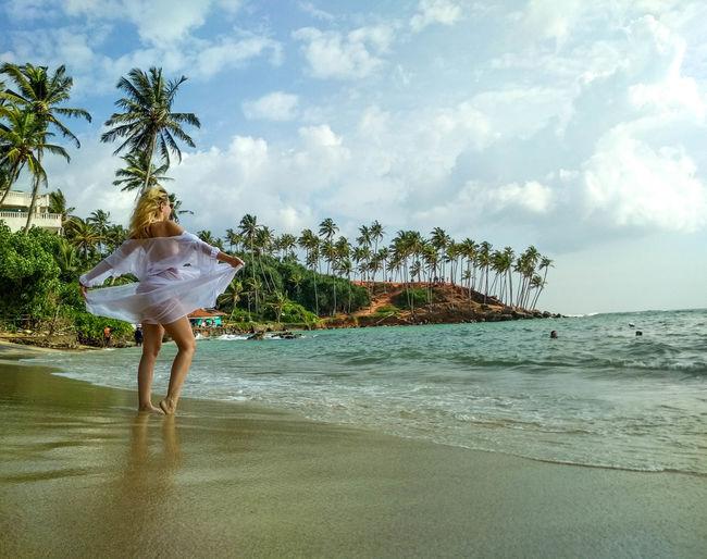 Woman on beach by sea against sky