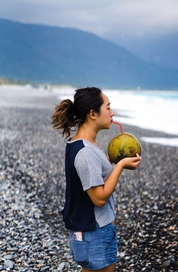 Woman drinking coconut water while standing at beach