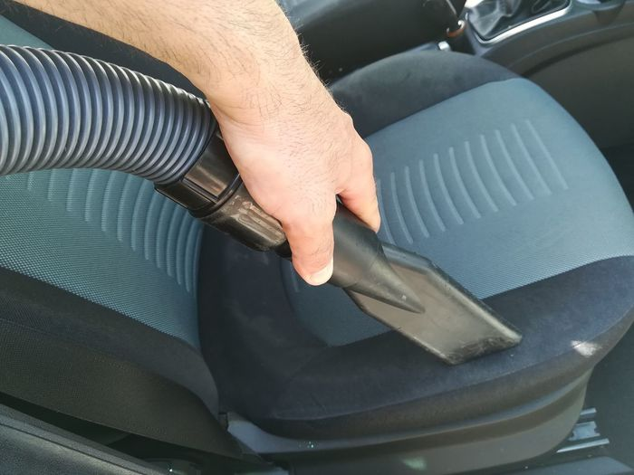 Cropped hand of man cleaning vehicle seat with vacuum cleaner in car