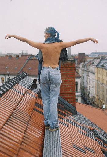 Rear view of man standing on roof