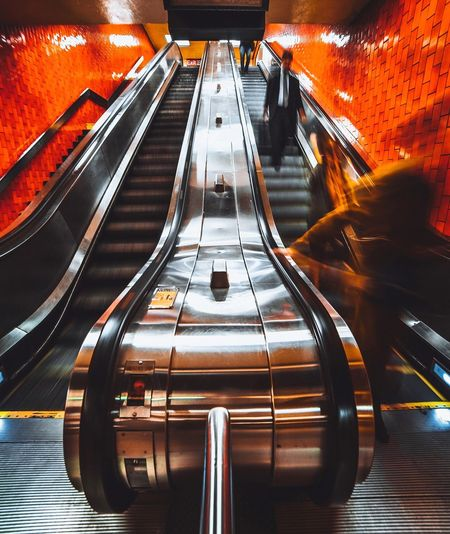 Blurred motion of people on escalator at subway station