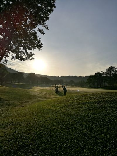 People on golf course against sky during sunset
