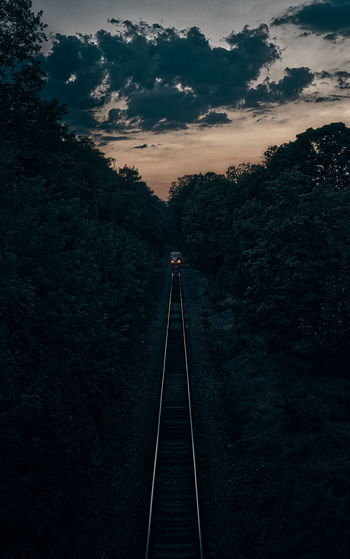 Train on railroad track amidst trees against sky during sunset
