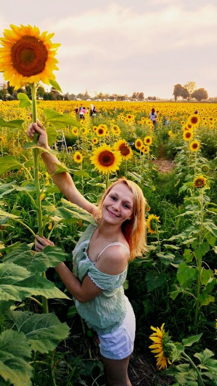 flower, field, rural scene, agriculture, crop, one person, growth, only women, smiling, one woman only, adult, happiness, nature, cloud - sky, plant, outdoors, adults only, portrait, people, day, cheerful, looking at camera, cereal plant, young adult, beautiful woman, one young woman only, sky, human body part, grass, freshness, blond hair, young women, beauty in nature, flower head