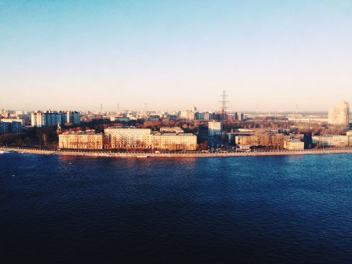 River by cityscape against clear sky