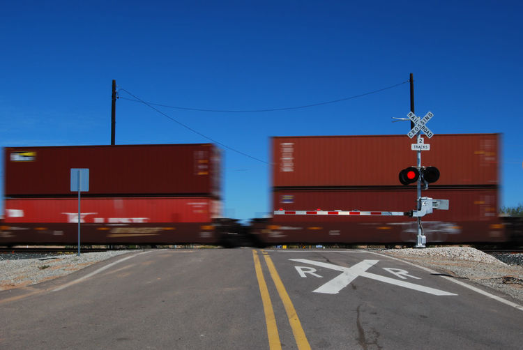 Train Passing By Railroad Crossing Against Clear Blue Sky