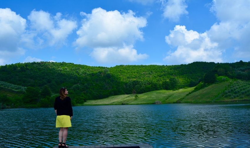 Rear View Of Mid Adult Woman Standing By Lake Against Blue Sky