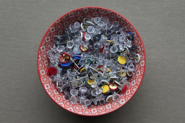 Variety of thumbtacks in container on table
