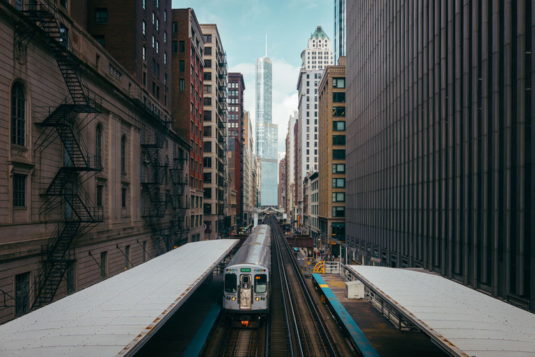 Railroad station amidst buildings in city against sky