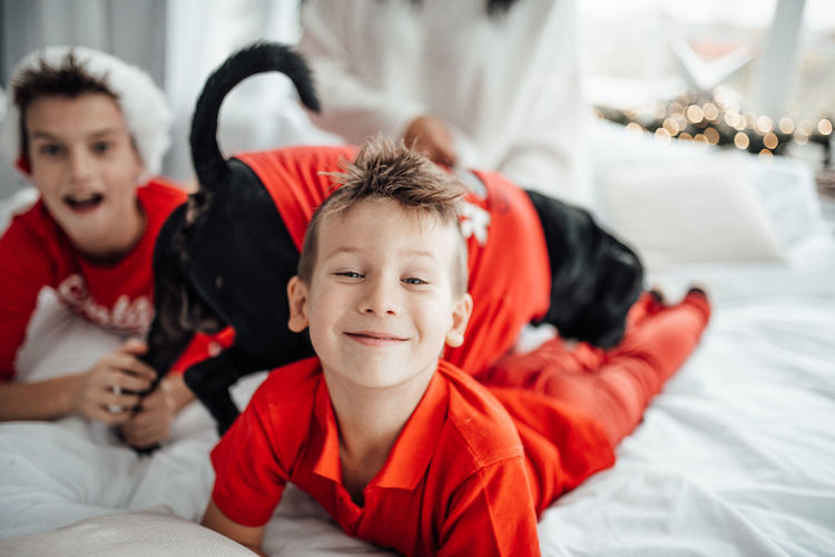 Portrait of smiling kids with dog on bed at home