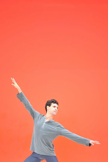 Young Man Dancing Against Orange Background