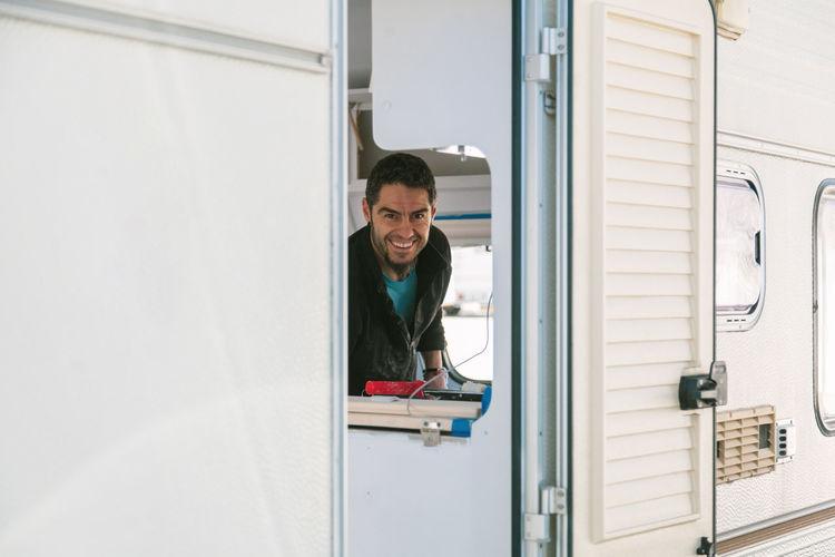 Portrait of smiling man in camper trailer