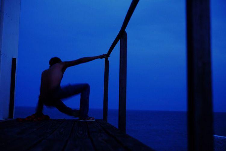 Man on sea against clear blue sky