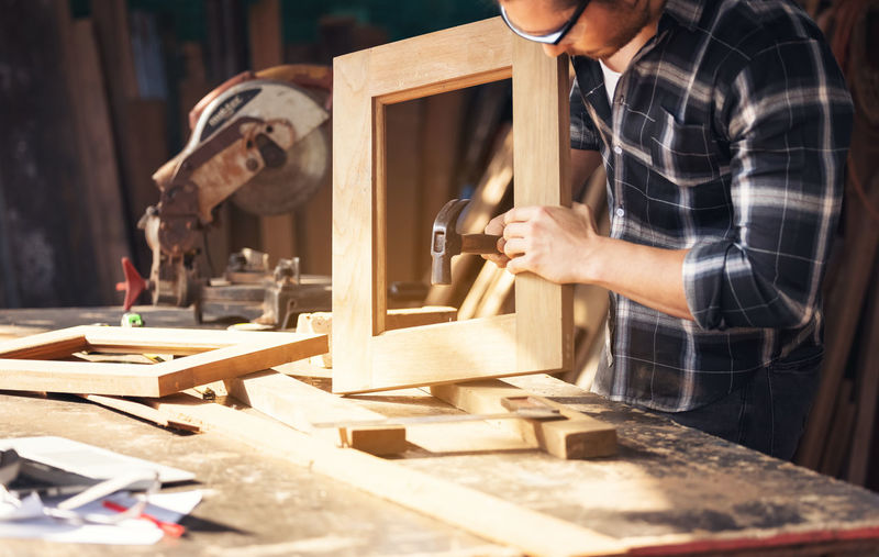 Carpenter working on woodworking machines in carpentry shop. a man works in a carpentry shop. person