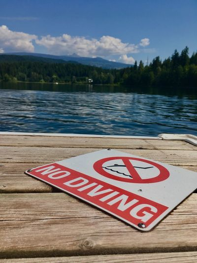 No diving Landscape Diving Dock Beautyineverything Nodiving Lake View Lake Water Communication Sign Text No People Lake Information Warning Sign Sky Nature Tranquility Outdoors Wood - Material Cloud - Sky Western Script Guidance