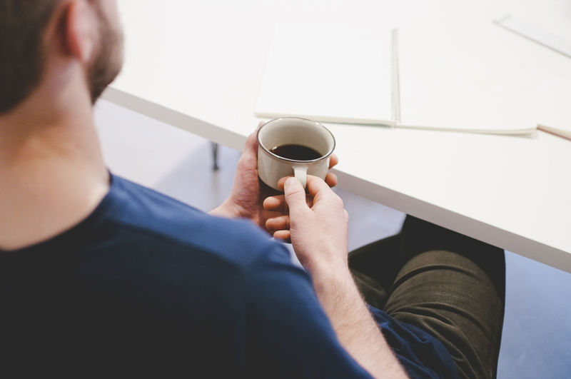 Rear view of man holding coffee cup