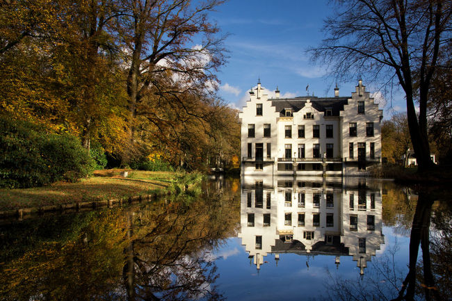 Castle Staverden reflecting in the moat and surrounded by autumn colored trees Architecture Autumn Bare Tree Building Exterior Built Structure Day Nature No People Outdoors Reflection Sky Travel Destinations Tree Water Waterfront