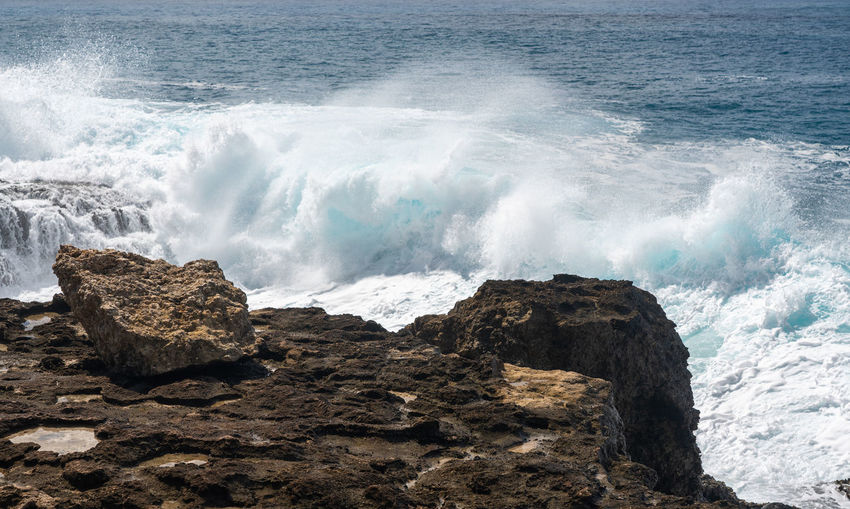 Large waves crash on the shoreline of ka'ena point on the extreme west coast of oahu in hawaii