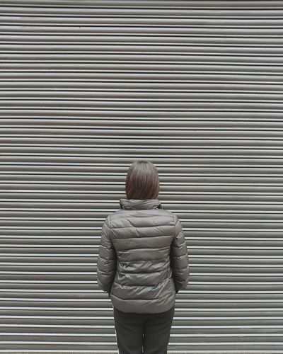 Rear view of woman standing against shutter