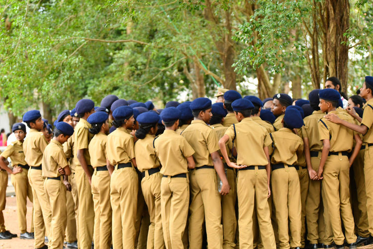 Children wearing police uniforms standing against trees