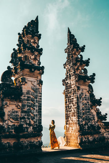 Woman standing amidst built structure at temple against sky
