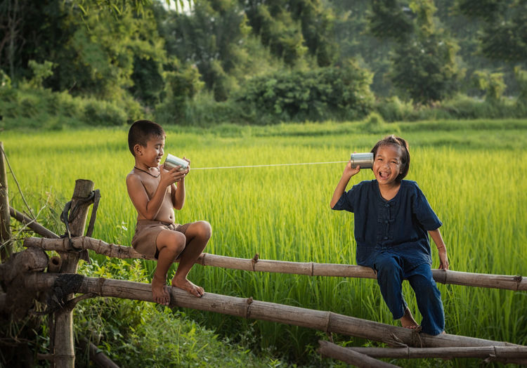 Siblings playing with tin can phone on grassy field