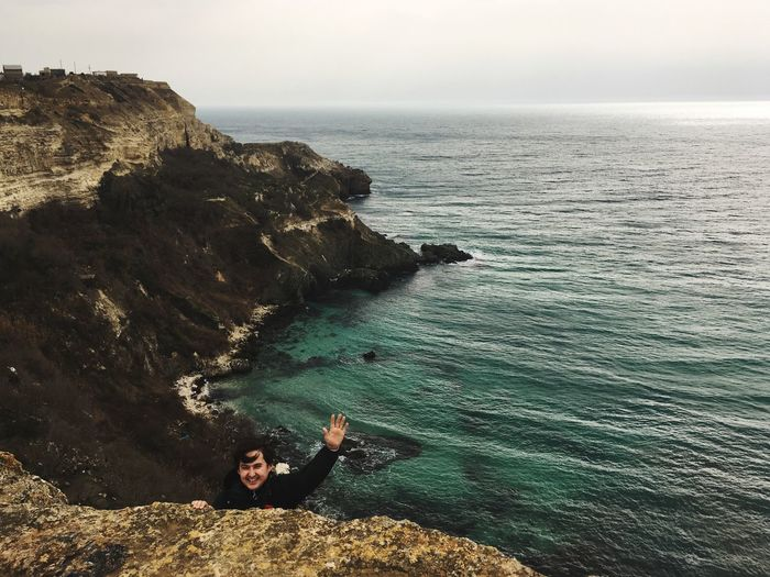 Portrait Of Smiling Man Gesturing While Climbing On Cliff Against Sea