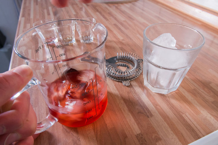 Mixing a negroni cocktail next to a glass full of ice cubes and strainer barspoon
